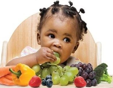 Little girl eating grape