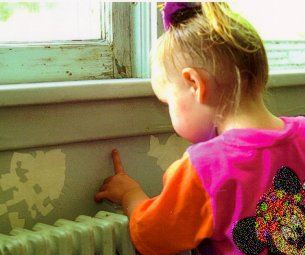 toddler touching paint on wall